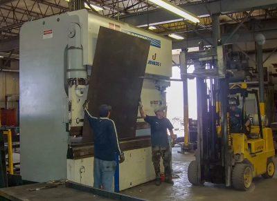 Worker Using Press Brake to Bend Metal