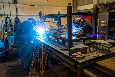 Welders working together to make a work table